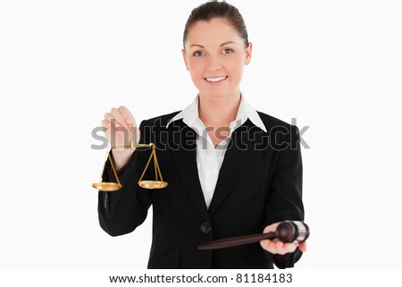 Beautiful woman in suit holding scales of justice and a gavel while standing against a white background - stock photo