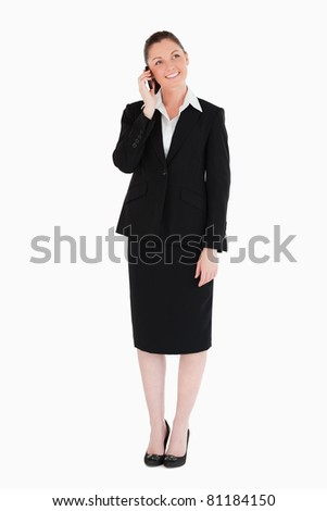 Beautiful woman in suit on the phone while standing against a white background - stock photo