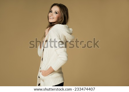 Beautiful woman in sweater is posing in studio, winter fashion - stock photo