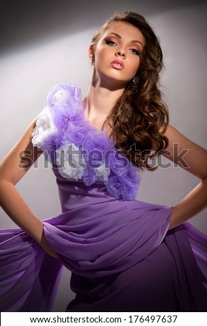 beautiful woman in the purple dress with a gray background - stock photo