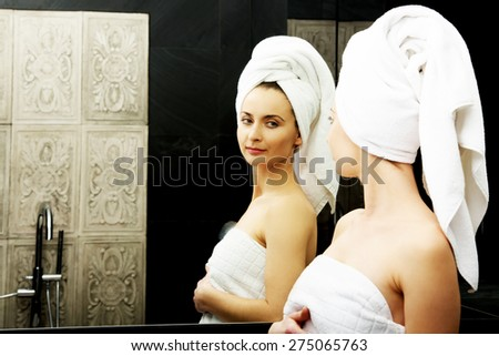 Beautiful woman in towel looking at the mirror. - stock photo