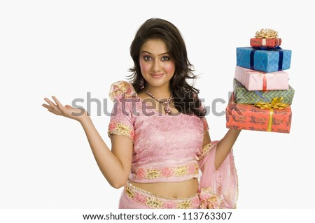 Beautiful woman in traditional dress holding gifts and smiling - stock photo
