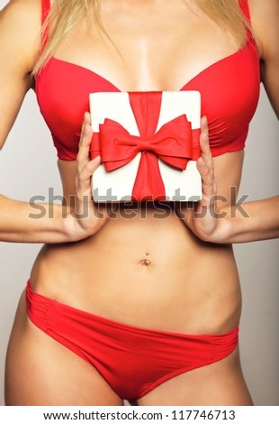 Beautiful woman in underwear holding a gift - stock photo