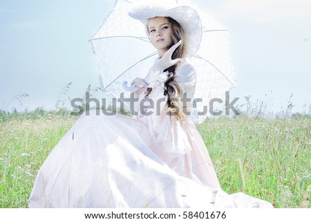 Beautiful woman in vintage dress sitting in a field - stock photo