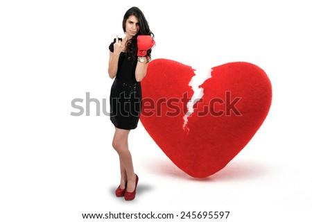 Beautiful woman in wearing a boxing glove in front of a broken heart - heart breaker - stock photo