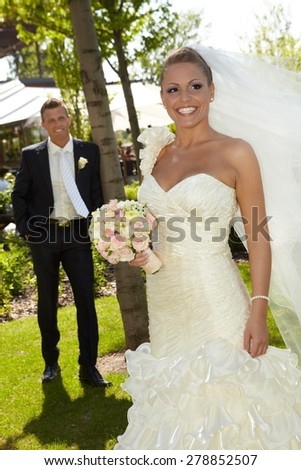 Beautiful woman in wedding gown smiling happy on wedding-day, wearing long veil, groom at background. - stock photo