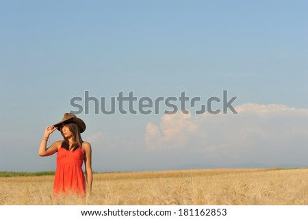 Beautiful woman in wheat yellow field and blue sky - stock photo