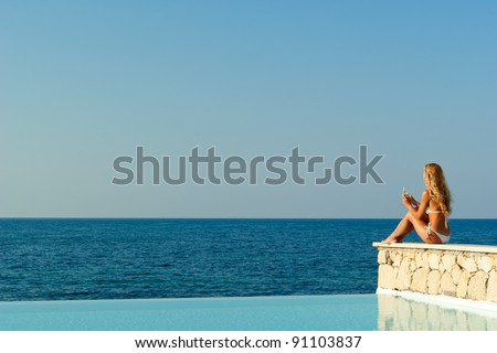 Beautiful woman in white bikini sitting near infinity pool and looking to sea and horizon. Crete. Greece - stock photo