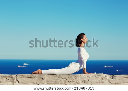 Beautiful woman in white clothes seated in yoga pose on blue sea background, healthy young woman meditating yoga enjoying amazing view of sea from high, practicing yoga at sunny day, feeling healthy - stock photo