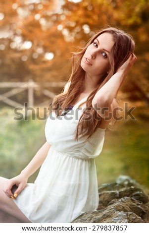 Beautiful woman in white dress in autumn forest - stock photo