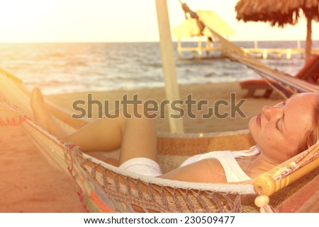 Beautiful woman in white dress on hammock under the sun on the beach - stock photo