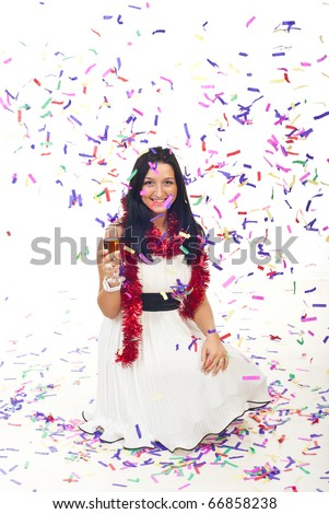 Beautiful woman in white dress sitting on white floor and holding  a glass with champagne while many confetti falling down  over her - stock photo