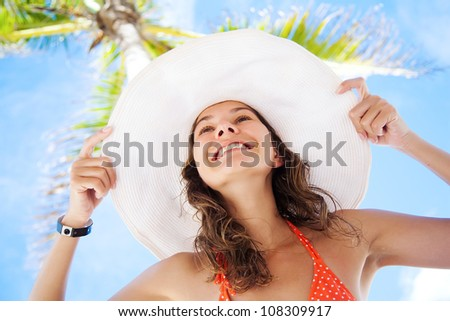 Beautiful woman in white hat on the background of palm and blue sky - stock photo