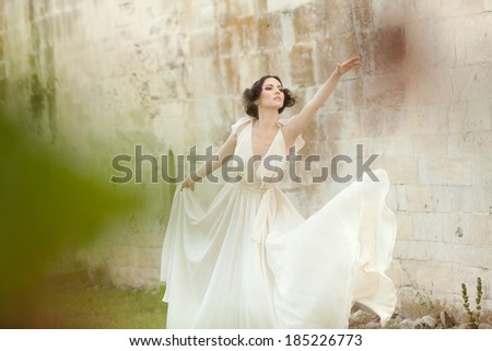 Beautiful woman in white long dress assuming a ballet position, arm stretched, leaning forward  - stock photo