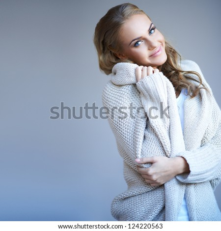 Beautiful woman in winter fashion snuggling up in the warmth of her stylish knitted wool jersey with a smile of pleasure - stock photo