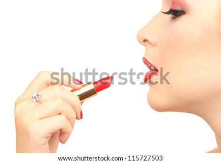 beautiful woman is applying her lips with red lipstick - stock photo