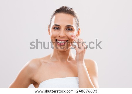 Beautiful woman is  applying lotion on her face. - stock photo