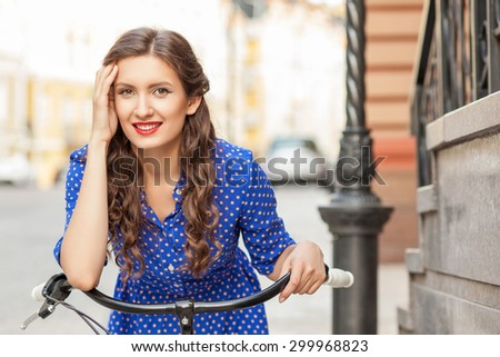 Beautiful woman is cycling in city. She is looking at the camera with pleasure and smiling. The lady is touching her hair shyly. Copy space in right side - stock photo