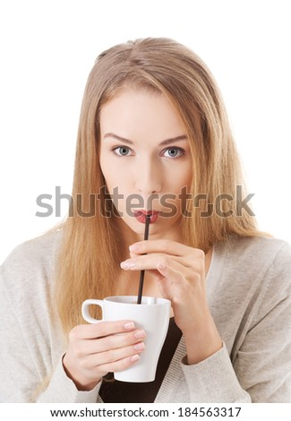Beautiful woman is drinking from a cup with a straw. Isolated on white. - stock photo