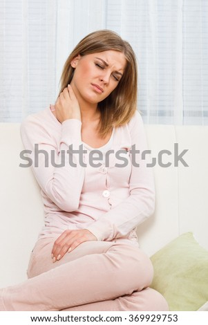 Beautiful woman is having pain in her neck.Neck pain - stock photo