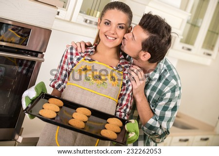 Beautiful woman is holding hot roasting pan with cookies. Happy husband is kissing her. - stock photo