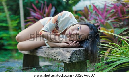 Beautiful woman is laying on the old wooden bench on the tropical garden background. Focus point on the face. - stock photo