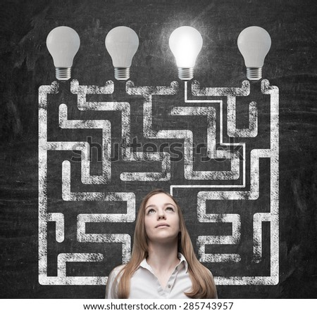 Beautiful woman is looking for the way how to solve the maze and reach the right light bulb as a concept of the perfect business solution. - stock photo