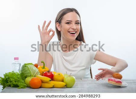 Beautiful woman is pushing the plate with donuts aside. She decided to eat only healthy vegetables and fruits. The lady is smiling and happily gesturing. Isolated on a white background - stock photo
