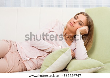 Beautiful woman is resting at sofa.Woman napping - stock photo