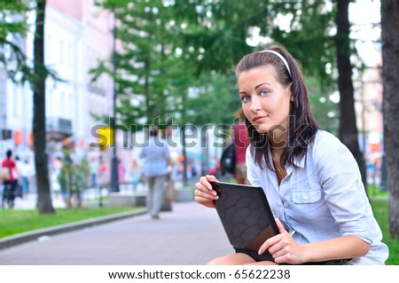 beautiful woman is sitting in city with laptop and looking at camera - stock photo