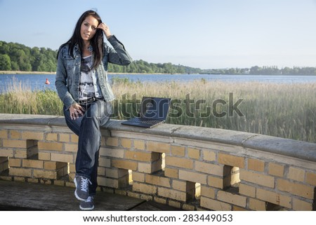 Beautiful woman is sitting on a wall near by a lake with a notebook - stock photo