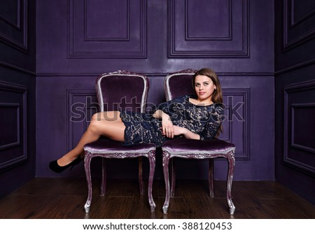Beautiful woman is sitting on two chairs, a concept - stock photo