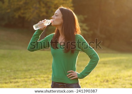 Beautiful woman is standing in the park and drinking water.Refreshment - stock photo