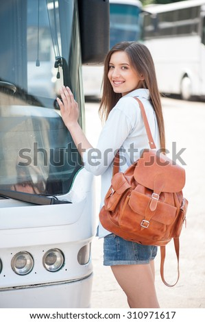 Beautiful woman is standing near a bus. She is leaning on the front of it and smiling. The woman begins her journey - stock photo
