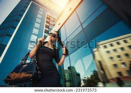 beautiful woman is walking in the modern city - stock photo