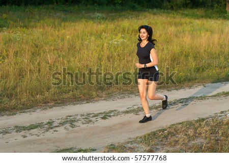 Beautiful woman jogging outdoors in forest road - stock photo