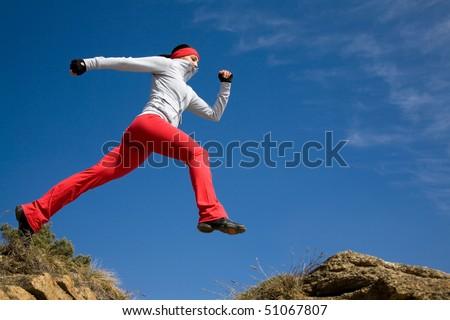 Beautiful woman jumping against blue sky - stock photo