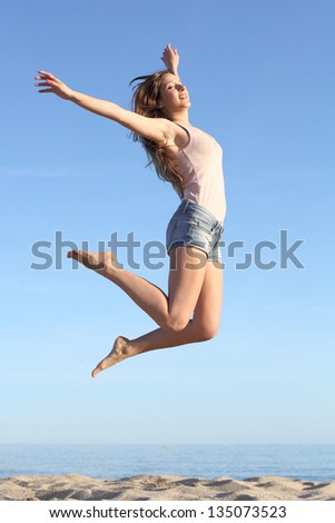 Beautiful woman jumping happy on the beach with a blue sky in the background - stock photo