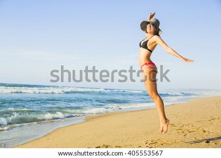 Beautiful woman jumping on the beach - stock photo