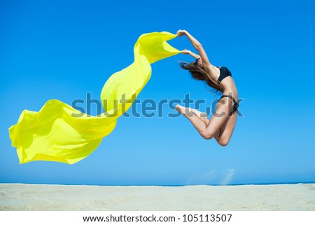 Beautiful woman jumping on the beach with bright yellow fabric - stock photo