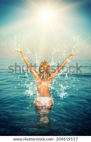 Beautiful woman jumps out of the sea leaving a big splash - stock photo