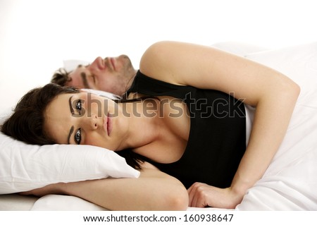 Beautiful woman laid in a white bed awake next to her sleeping boyfriend isolated on a white background - stock photo