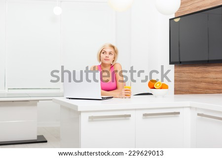 beautiful woman laptop sitting table home, pretty girl using computer dream look up copy space, modern bright room - stock photo