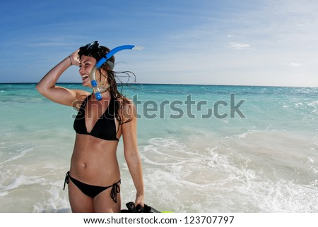 Beautiful woman laughing with snorkeling gear on a beach - stock photo