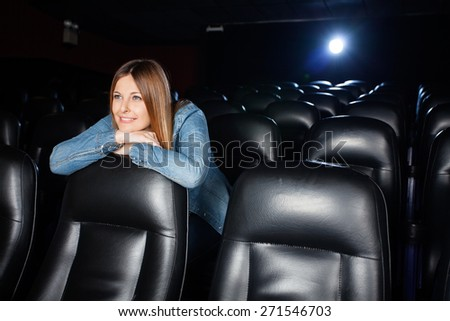 Beautiful woman leaning on seat while watching movie at cinema theater - stock photo