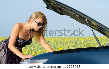 Beautiful woman leaning over with her hand in the engine compartment looking at her car engine near a field of sunflowers - stock photo