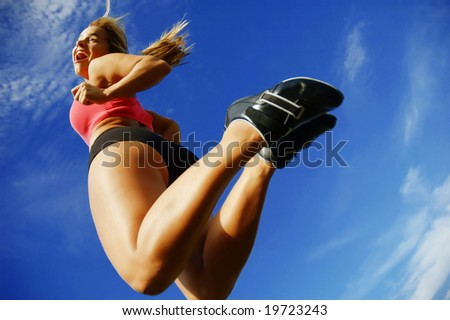 Beautiful woman leaping into air against sky, low angle. - stock photo