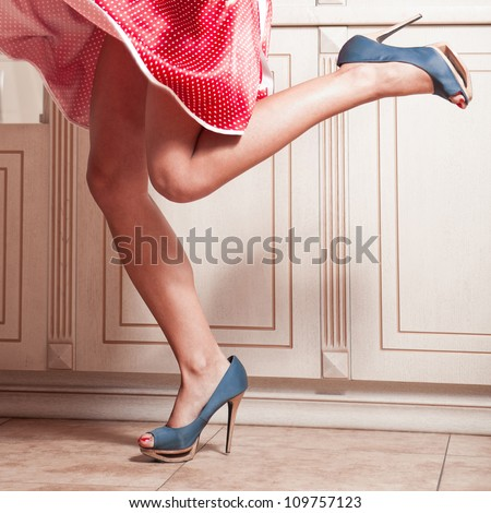 Beautiful woman legs in red dress with blue high heel shoes - stock photo
