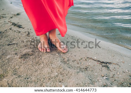Beautiful woman legs on the beach at sunset - stock photo