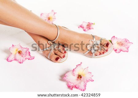 Beautiful woman legs with red manicure on the feet and flowers - stock photo